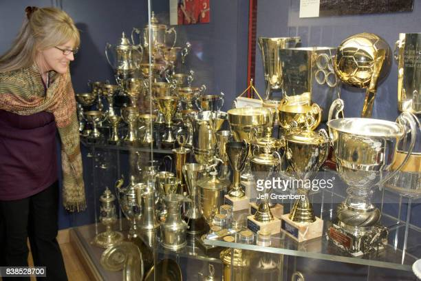 A woman looking at the trophy case at Manchester United Football Club at the Old Trafford Stadium