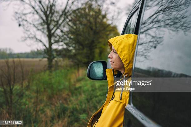 woman looking at the view from her campervan in wet weather - yellow stock pictures, royalty-free photos & images