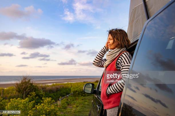 woman looking at the view from her campervan - sunset stock pictures, royalty-free photos & images