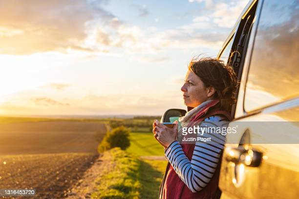 woman looking at the view from her campervan - lifestyle stock pictures, royalty-free photos & images