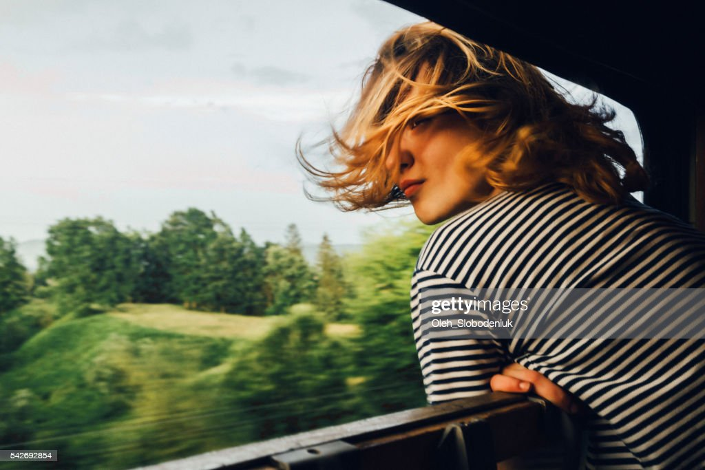Woman looking at the view from train : Stock Photo