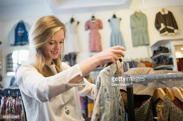 woman looking at top garment - sean malyon stock pictures, royalty-free photos & images