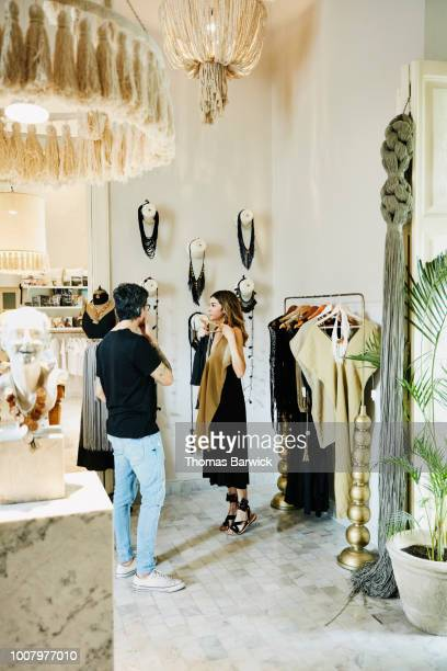 woman looking at top in mirror while shopping with husband in boutique - women in transparent clothing stock photos and pictures