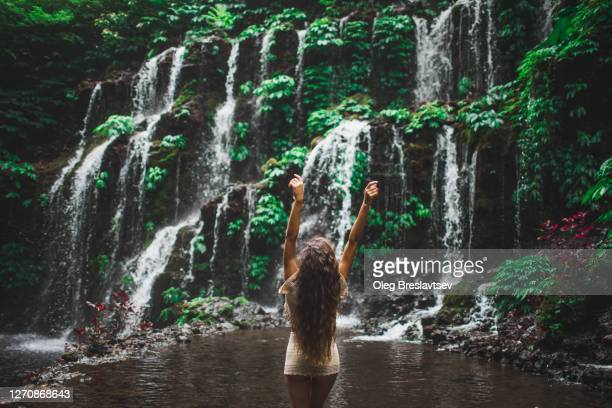 woman looking at tropical waterfall in bali jungle. view from behind. - behind waterfall stock pictures, royalty-free photos & images