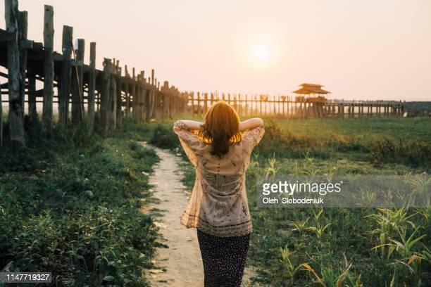 woman looking at u bein bridge in mandalay - myanmar culture stock pictures, royalty-free photos & images
