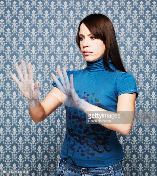 Woman looking at vanishing hands (Digital Composite)