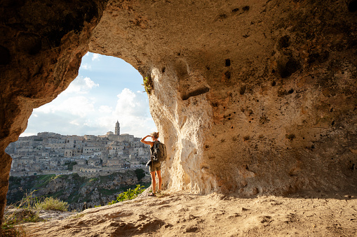 Woman looking at view from a cave of Matera, Basilicata, Italy 1040315976