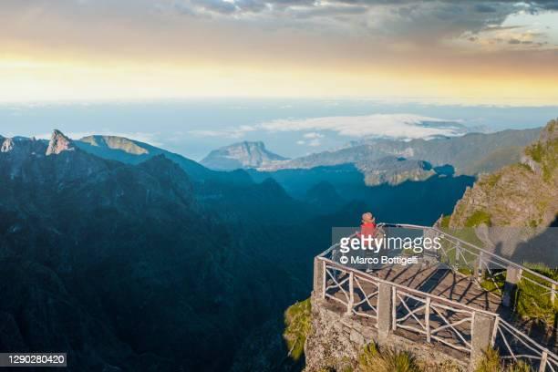 woman looking at view from a mountain lookout, madeira - madeira fotografías e imágenes de stock