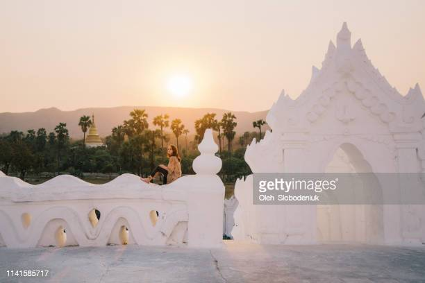 woman looking at view from walls of  white hsinbyume pagoda in mandalay - myanmar culture stock pictures, royalty-free photos & images