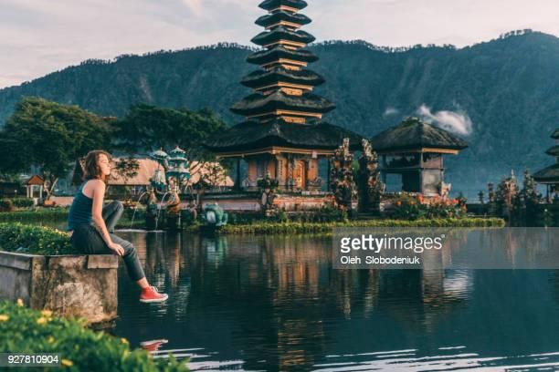 Woman looking at  view of Ulun Danu Temple  in  Bali  at sunrise