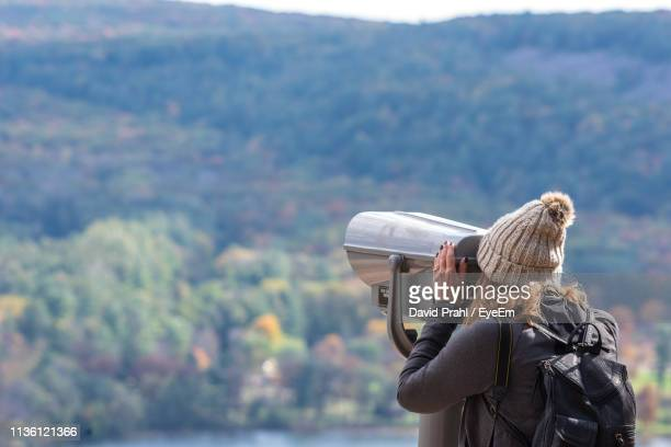 Woman Looking At View Through Telescope