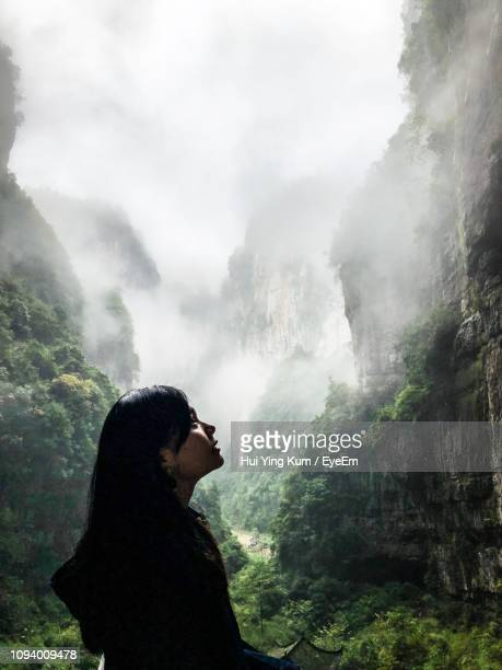 woman looking at view while standing by mountains in forest - chongqing stock photos and pictures