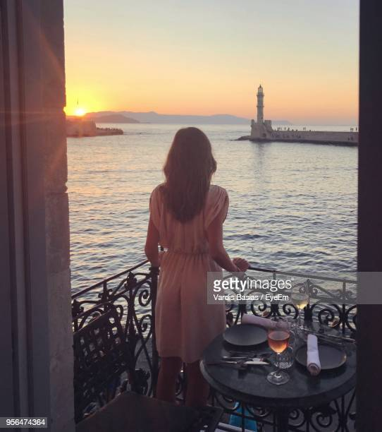 Woman Looking At View While Standing On Balcony During Sunset
