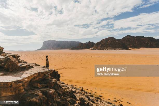 woman looking at  wadi rum desert from rock - jordan middle east stock pictures, royalty-free photos & images