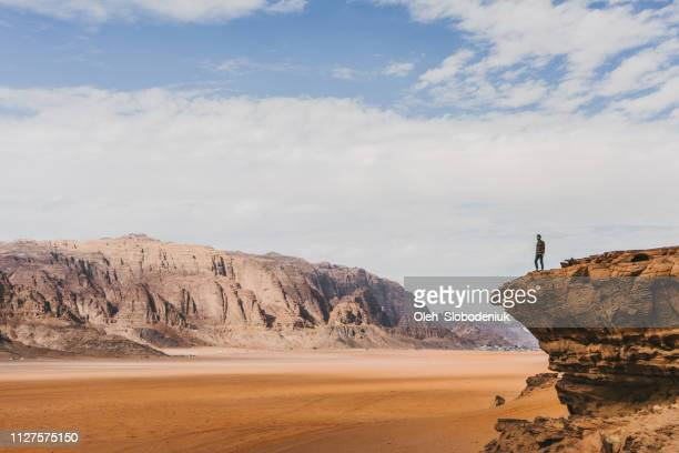 woman looking at  wadi rum desert from rock - rock formation stock pictures, royalty-free photos & images