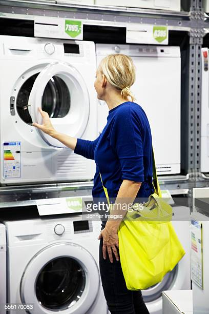 Woman looking at washing machine in shop