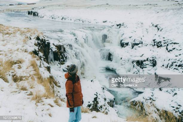 woman looking at  waterfall in winter - dettifoss waterfall stock photos and pictures