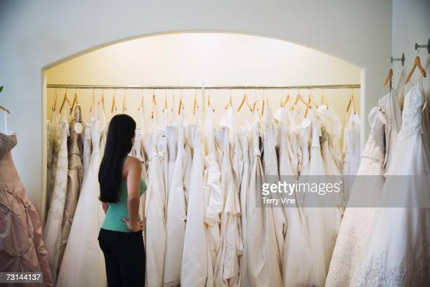 woman looking at wedding dresses on rack - wedding dress stock pictures, royalty-free photos & images