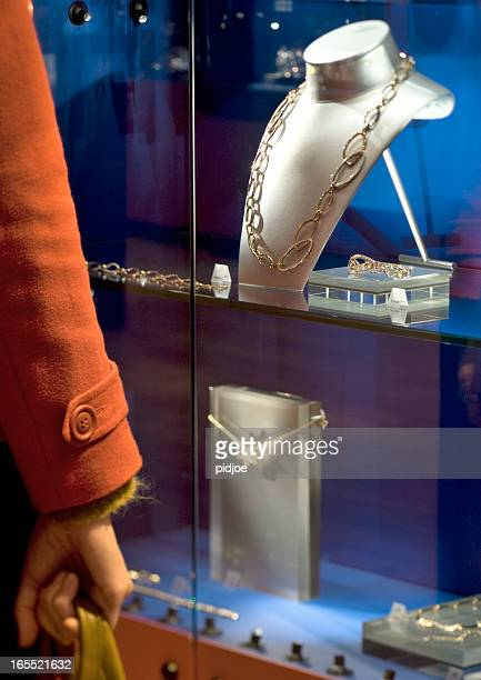 woman looking at window display of jewelry store