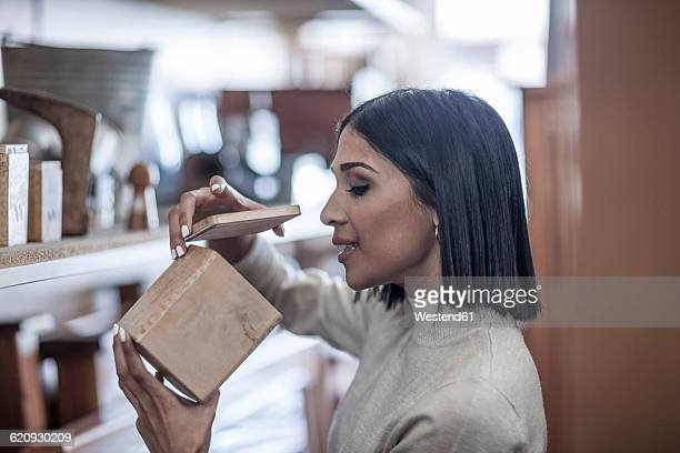Woman looking at wooden box in antique shop