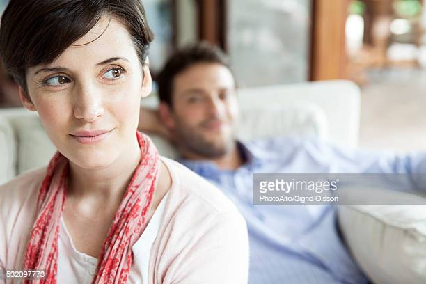 Woman looking away dreamily, man relaxing in background