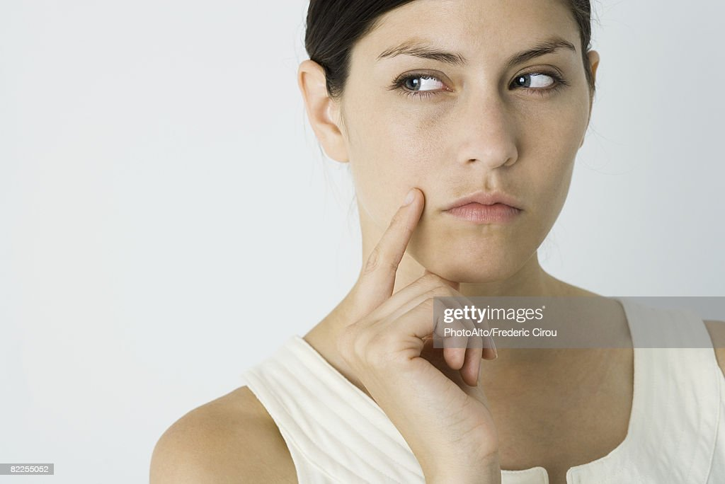 Woman looking away, hand under chin : Stock Photo