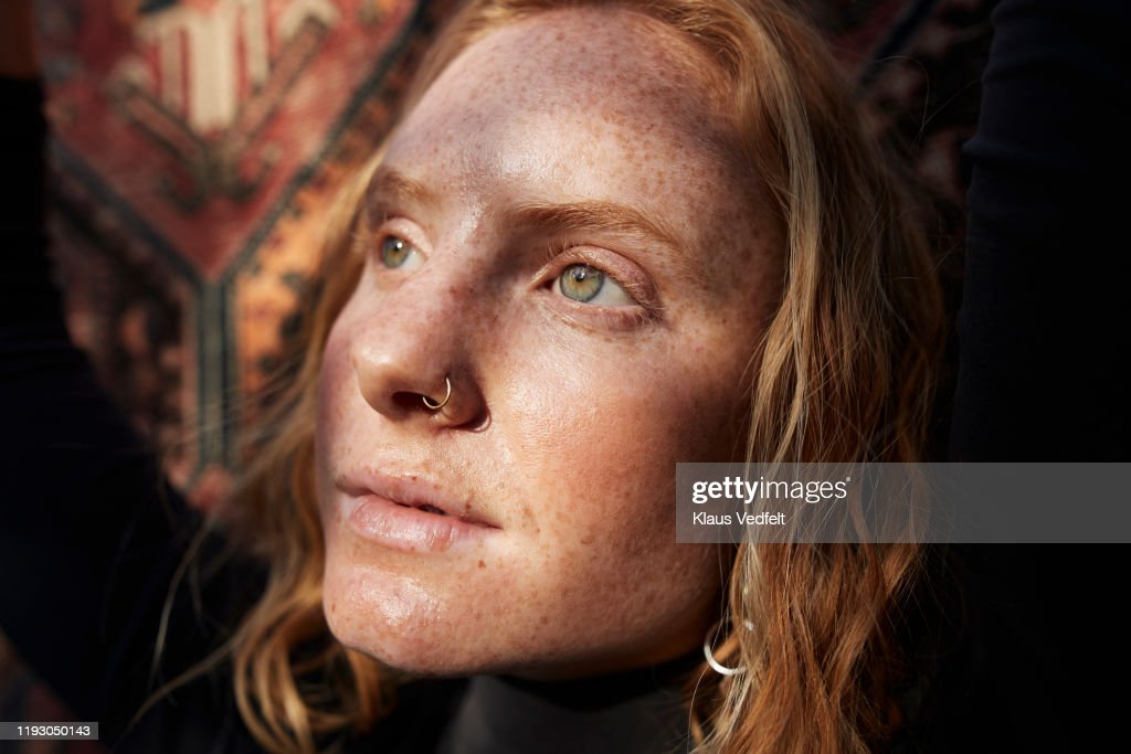 Woman looking away in sunlight against patterned wall : Stock Photo
