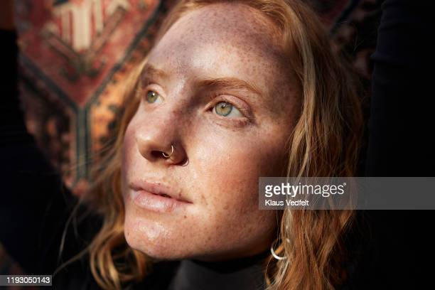 woman looking away in sunlight against patterned wall - green eyes stock pictures, royalty-free photos & images