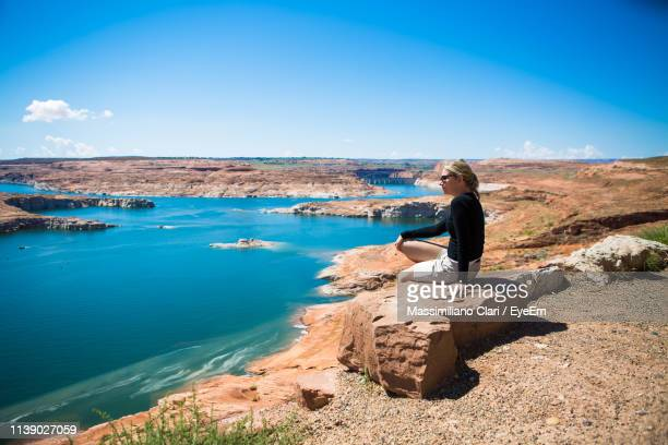 woman looking away sitting on rock by lake - lake powell stock pictures, royalty-free photos & images