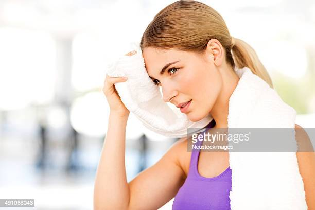 Woman Looking Away While Cleaning Sweat From Forehead At Gym