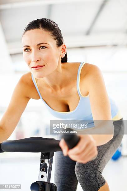 Woman Looking Away While Exercising On Bike In Gym