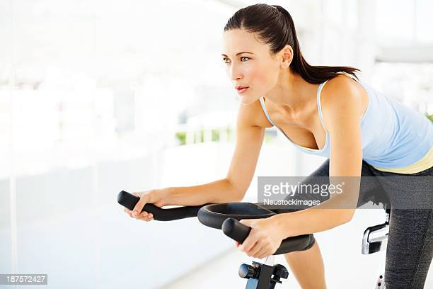 woman looking away while exercising on bike in gym - spinning stock pictures, royalty-free photos & images