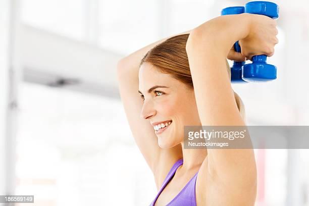 Mujer mirando de distancia, mientras hacen ejercicios con pesas en el gimnasio