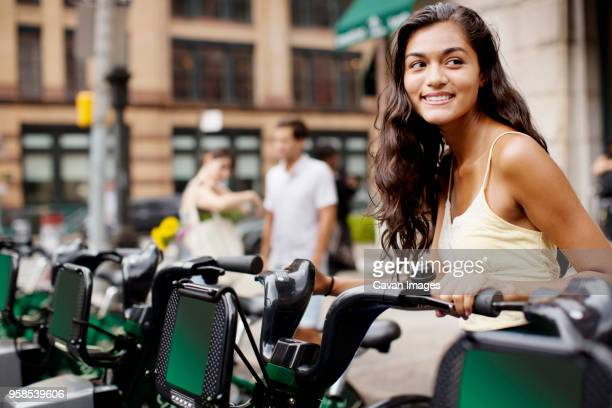 woman looking away while friends standing in background - bicycle parking station stock photos and pictures