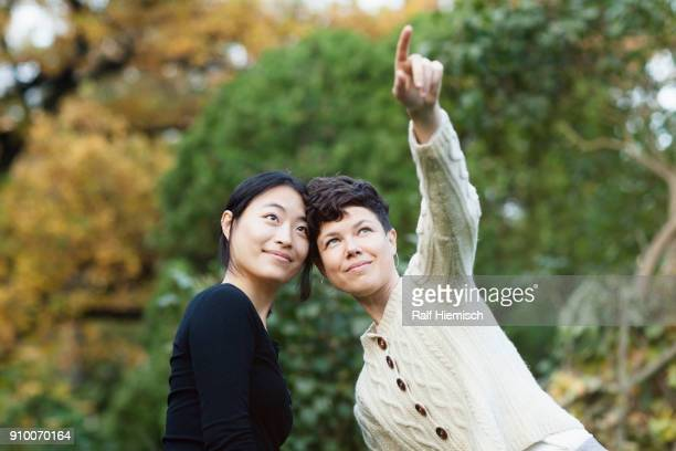 Woman looking away while pointing and showing to friend at park