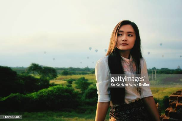 woman looking away while sitting against sky - ko ko htike aung stock pictures, royalty-free photos & images