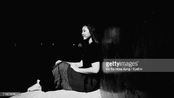 woman looking away while sitting against wall - ko ko htike aung stock pictures, royalty-free photos & images