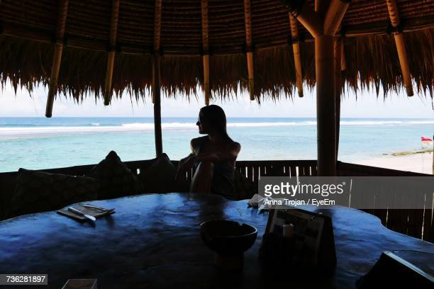 woman looking away while sitting at beach hut - anna cabana photos et images de collection