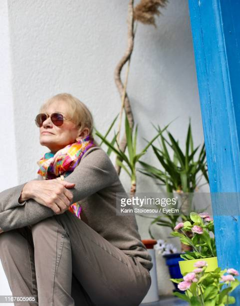 Woman Looking Away While Sitting By Potted Plants
