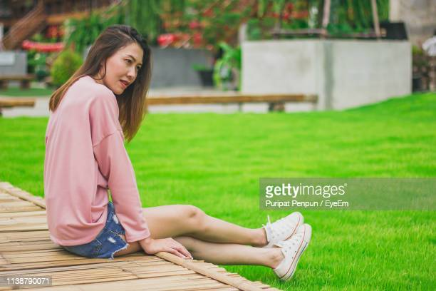 woman looking away while sitting on field - thai mueang photos et images de collection