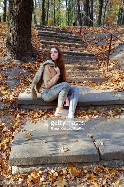 woman looking away while sitting on staircase - elena knouzi stock pictures, royalty-free photos & images