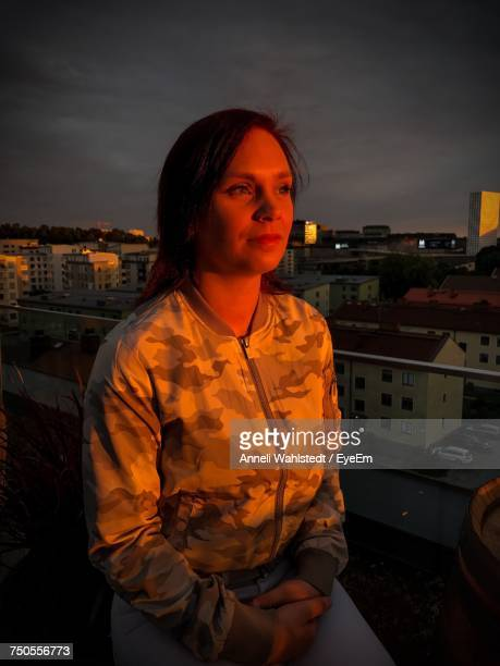 Woman Looking Away While Sitting On Terrace During Sunset