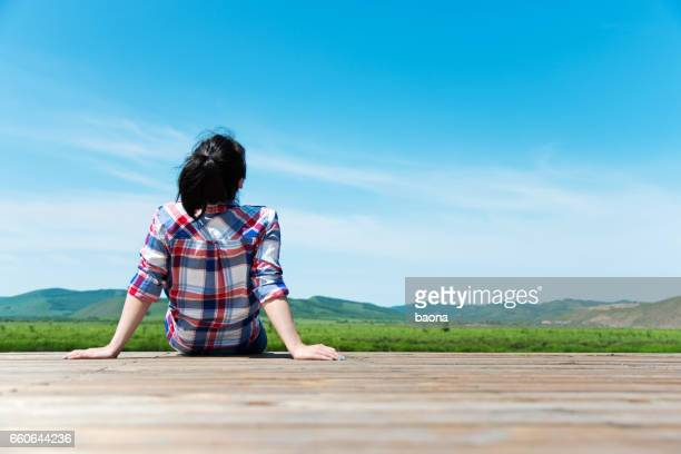 Woman looking away while sitting on wooden platform