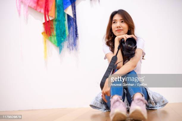 woman looking away while sitting with camera on floor against wall - anuwat somhan stock photos and pictures