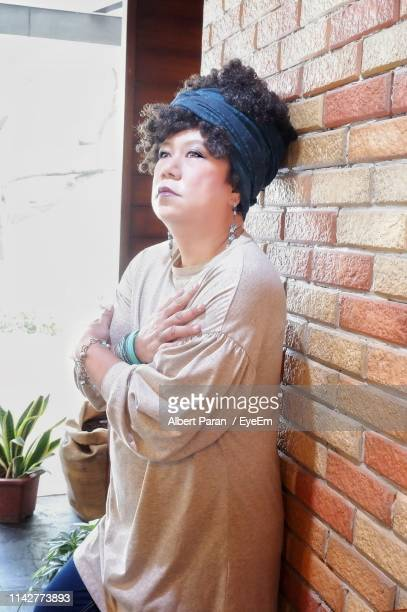 Woman Looking Away While Standing Against Brick Wall