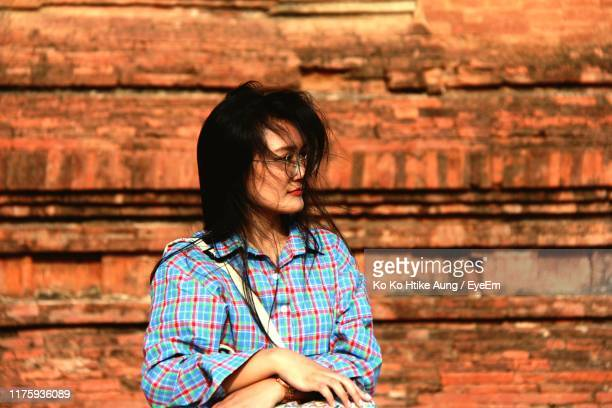 woman looking away while standing against wall - ko ko htike aung stock pictures, royalty-free photos & images
