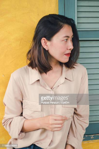 woman looking away while standing against wall - thai mueang photos et images de collection
