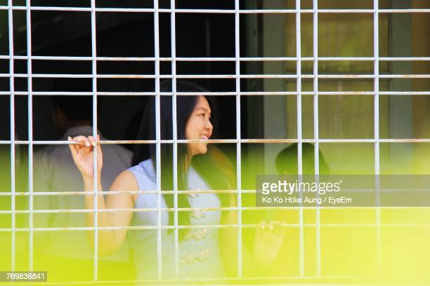 woman looking away while standing by window - ko ko htike aung stock pictures, royalty-free photos & images