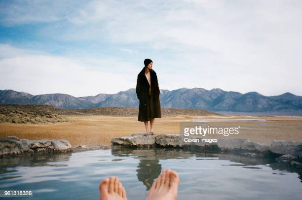 Woman looking away while standing on Mammoth Hot Springs against sky