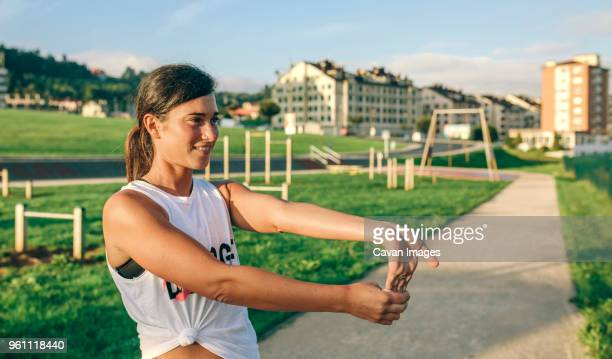 woman looking away while stretching wrist at park - wrist stock pictures, royalty-free photos & images